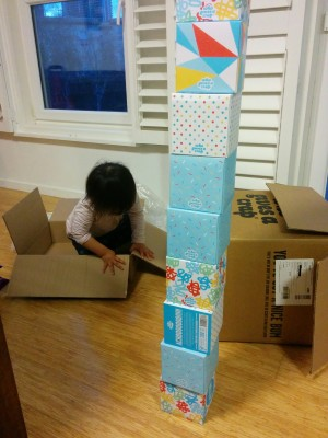 There is a colourful stack of tissue boxes. Behind the stack, there are two cardboard boxes. A toddler is sitting in one of them. Her face is not visible.