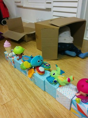 A range of colourful toys sit on top of a row of colourful tissue boxes. There are two boxes in the background. A toddler's legs and feet are sticking out of one of the boxes.