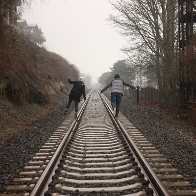 Two people standing on railway tracks next to each other. The tracks travel into the distance. Sky is gray and trees have lost their leaves.